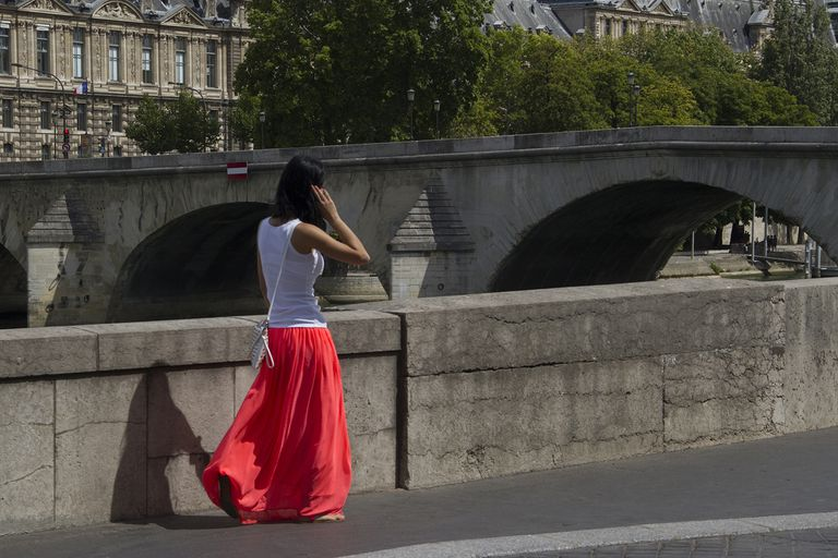 Shot from behind of woman walking down old street in a red maxi skirt and white tank top.