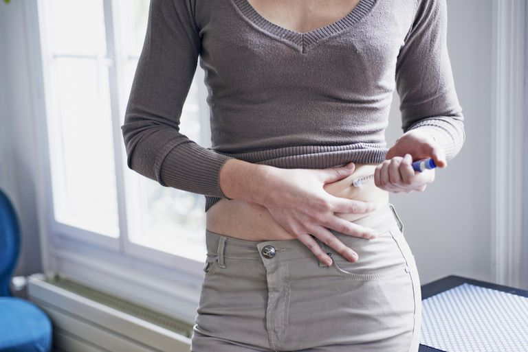 Woman injecting herself with insulin. France