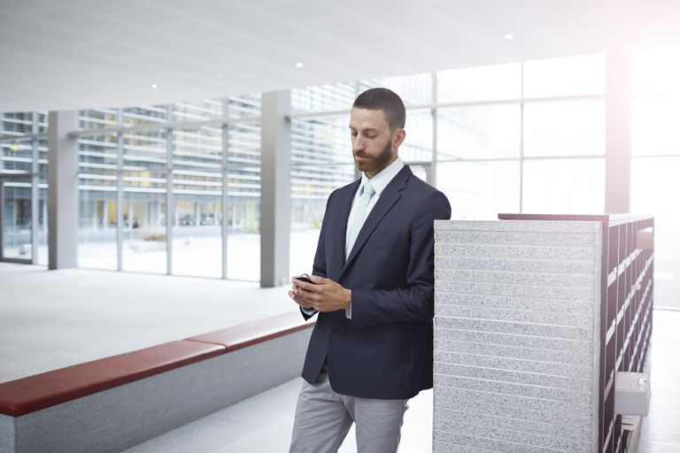 Creative businessman checking phone in hall