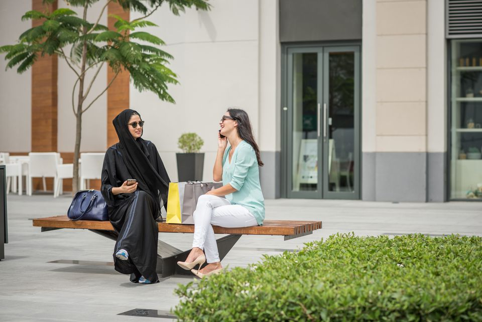 Young middle eastern woman wearing traditional clothing sitting on bench with female friend, Dubai, United Arab Emirates