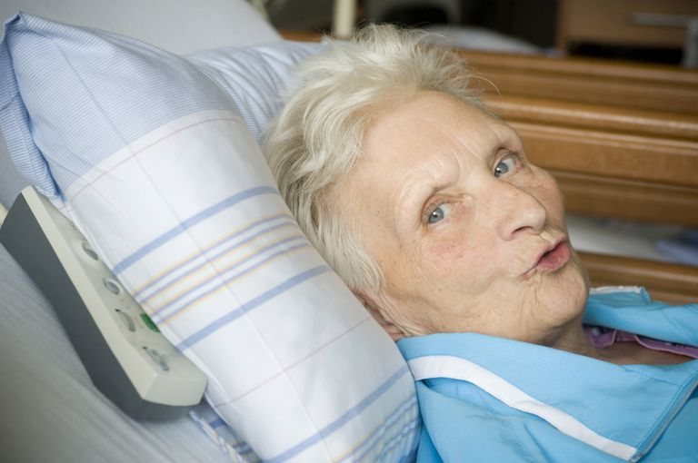 woman in hospital bed trying to speak