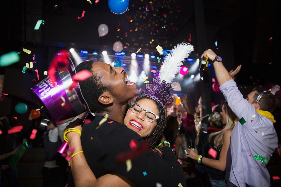 Confetti falling hugging couple enjoying New Year celebration.