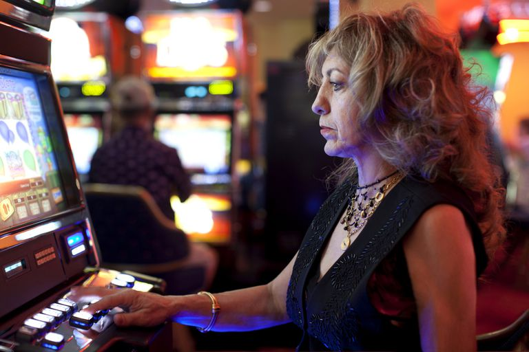 Caucasian woman playing slot machine in casino