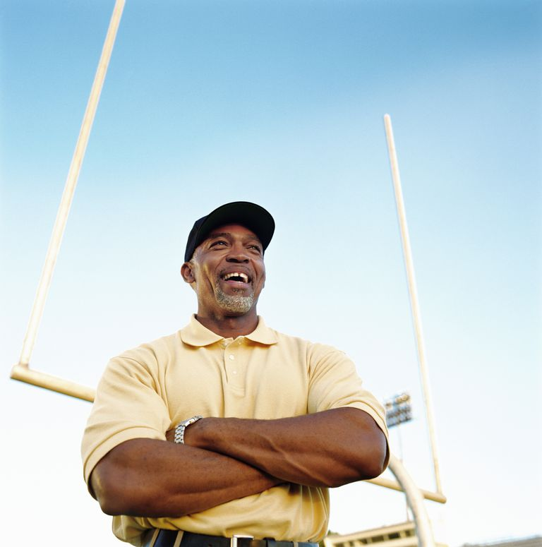 Football coach laughing, standing in front of goal post, low angle
