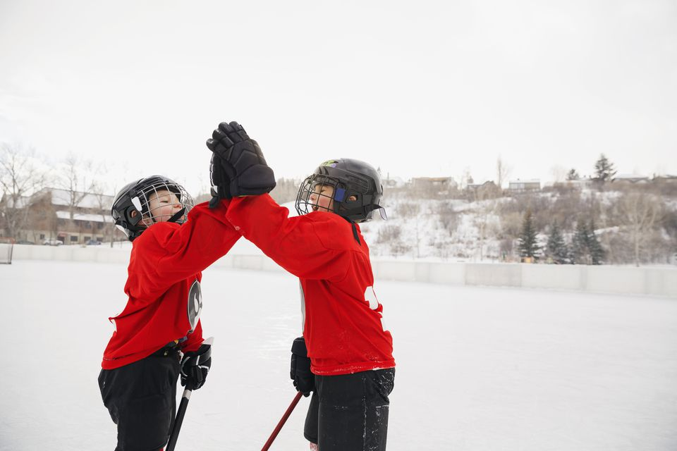 Ice hockey players giving high-five on rink