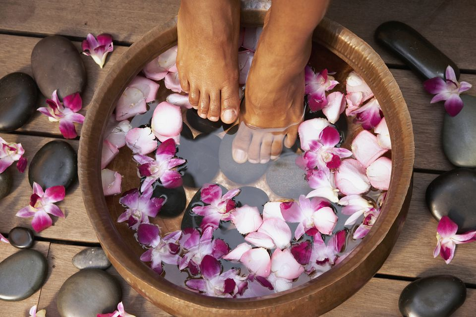 A woman's feet in a hydrating bowl as part of a pedicure procedure.