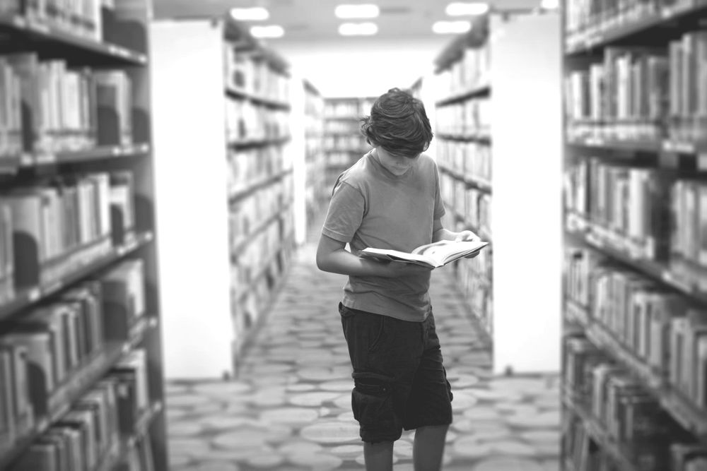 A boy reading a book in a library