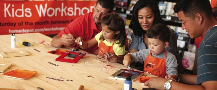 A family participating in a free Home Depot kids workshop.