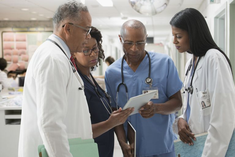 Doctors and nurses reviewing medical chart in hospital