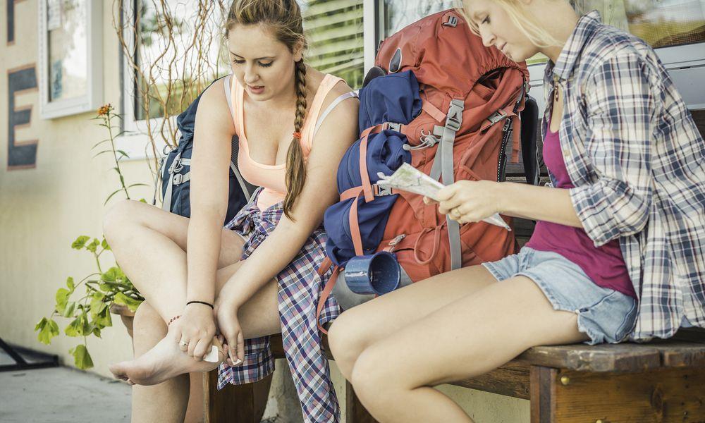 Teenage girl and young female hiker putting adhesive plaster on heel, Red Lodge, Montana, USA