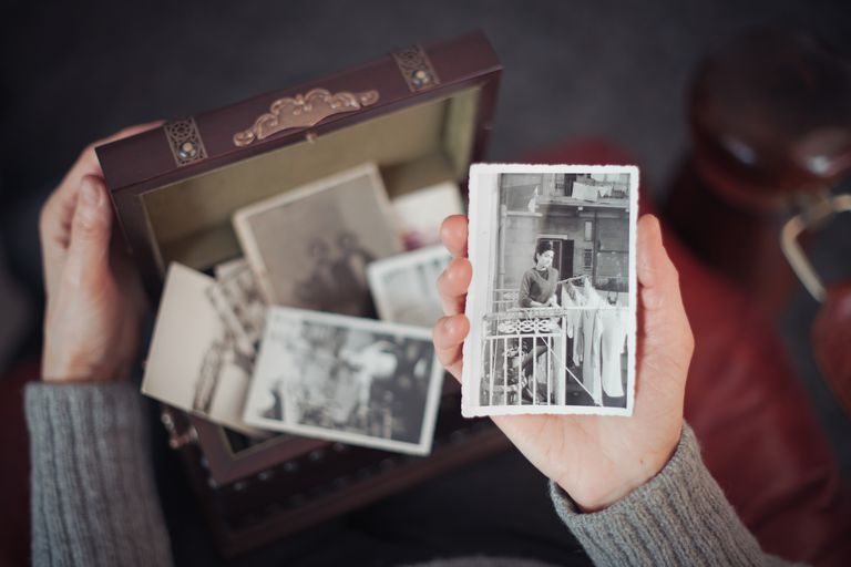 woman looking at old pictures of family members