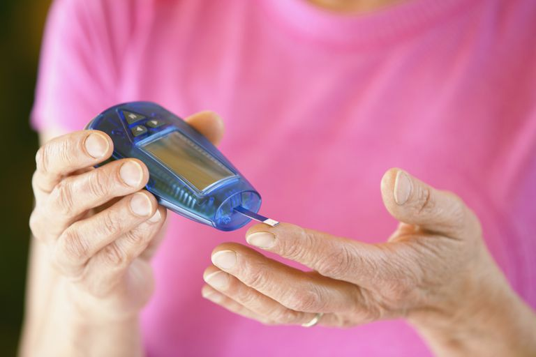 woman testing blood sugar with meter