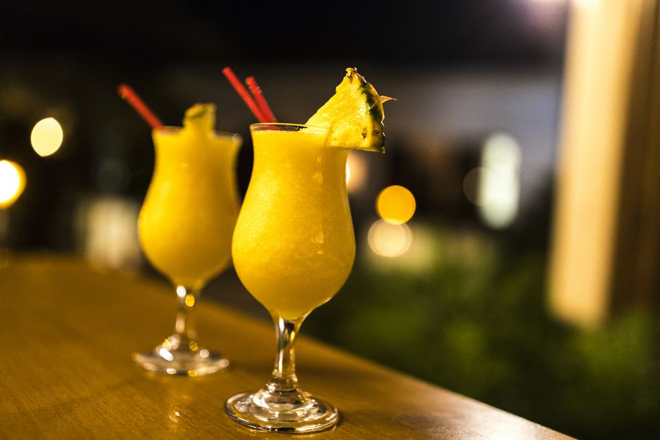 Two fresh mango daiquiris, decorated with a slice of pineapple, set on a bar counter and waiting to be savoured.