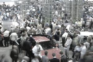 Crowd of people looking at cars at motorshow