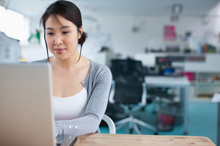 Smiling businesswoman working at laptop in office