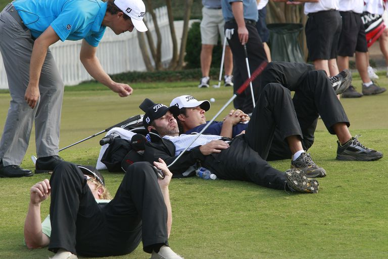 Golfer Parker McLachlin (L) sneaks up on napping caddies as they wait for word on when first round play would begin in the Viking Classic at the Annandale Golf Club