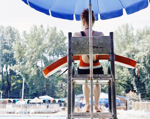 Teenage female lifeguard (14-16) watching pool, rear view
