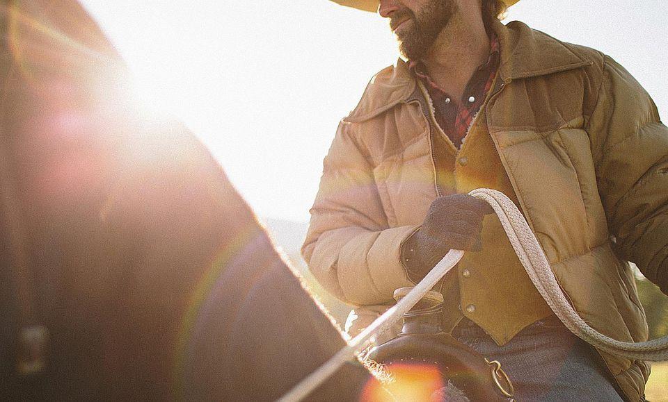 Man on horse using webbing reins.