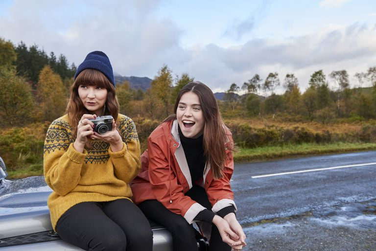 two girls sitting on the hood of their car with a camera