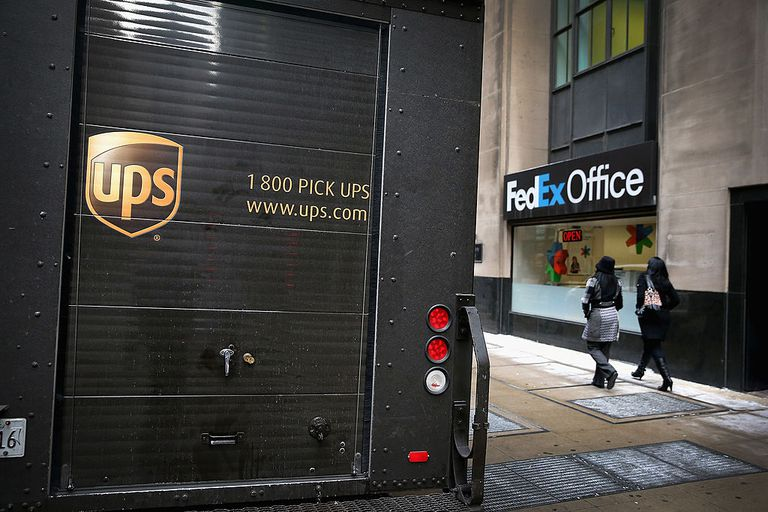 A UPS delivery truck sits in front of a FedEx Office store on December 26, 2013 in Chicago, Illinois.