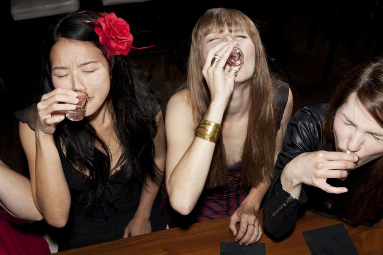 Women friends doing shots together at a bar