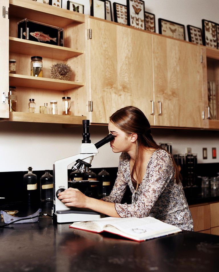 Teenage girl (14-16) using microscopes in science lab class