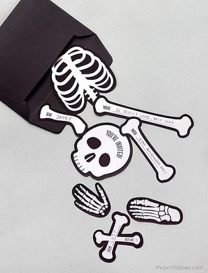 A Halloween invitation that's a paper skeleton in pieces.