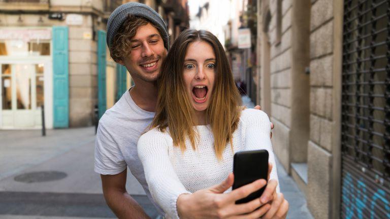 A man surprising a woman holding an iPhone