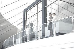 Businesswomen using digital tablet on atrium balcony