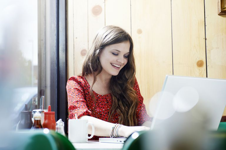 woman in cafe smiling using laptop