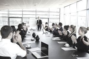 A presenter being applauded by his board of directors