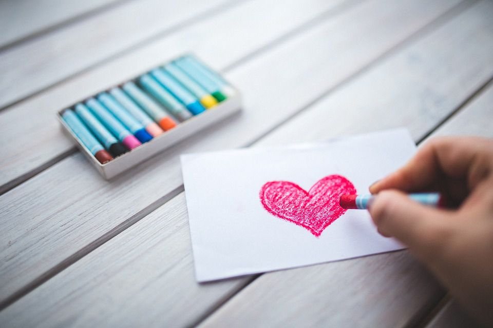 Child coloring heart with crayon.