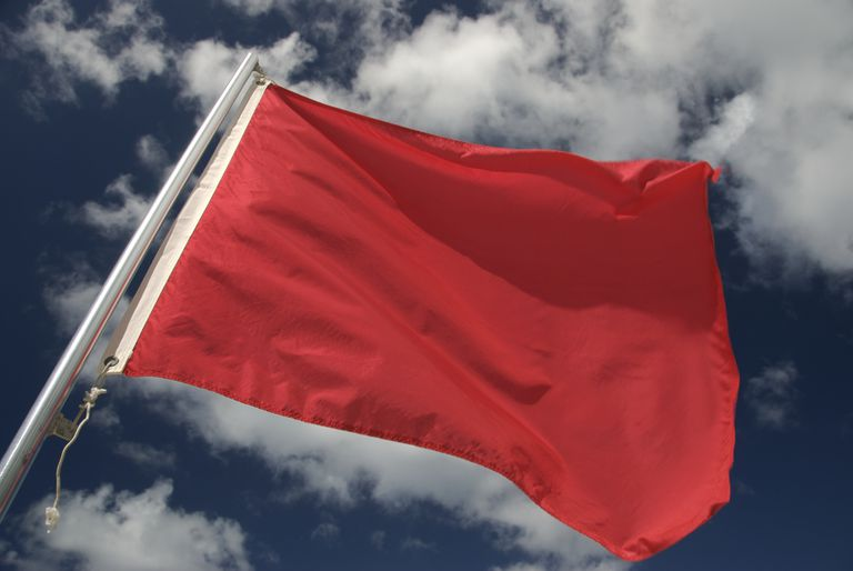red flag against clouds in sky