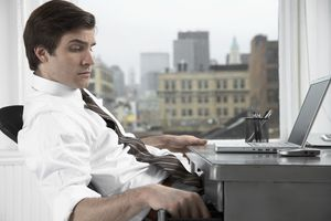 Man with laptop opening desk drawer