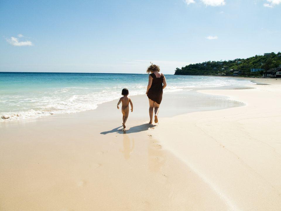Boy and mother running on beach, Port Antonio, Portland, Jamaica
