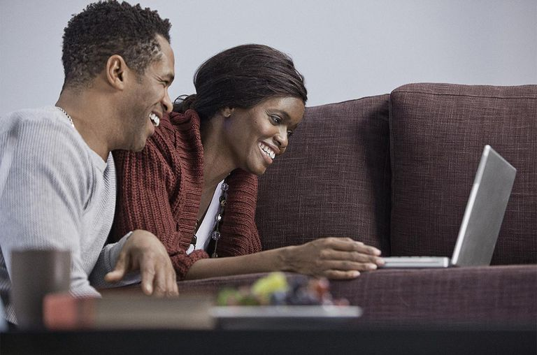 Couple using laptop together in living room