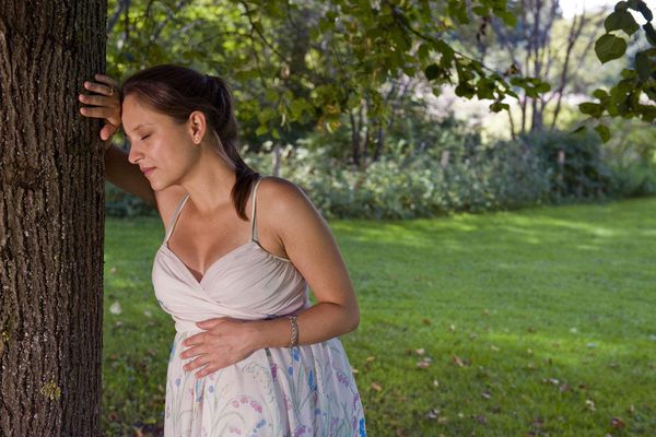 Pregnant woman leaning against tree in park