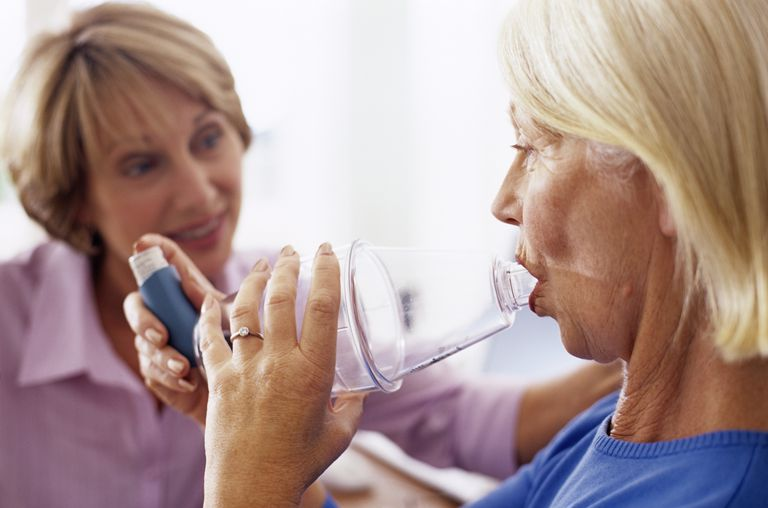 Woman using asthma spacer