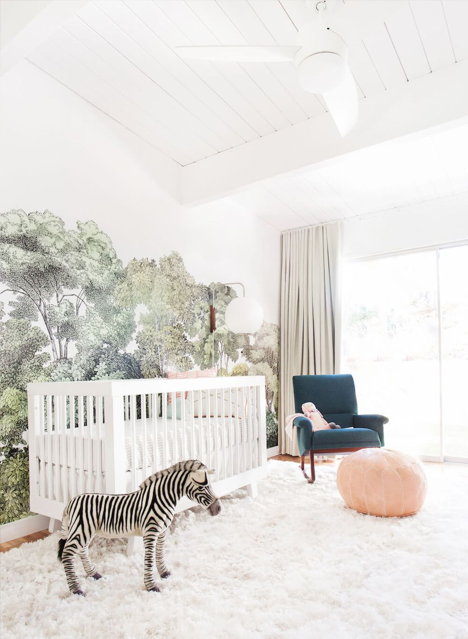 Simple white nursery space with dramatic wall mural