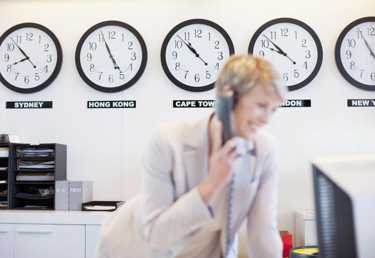 World clocks behind businesswoman in office