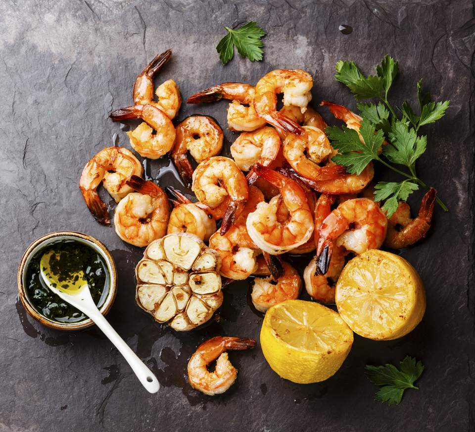 Prawns Shrimps roasted and served on stone slate with lemon and garlic close up