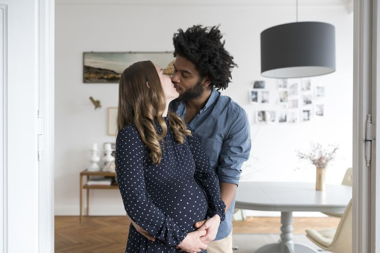 Kissing pregnant couple in living room