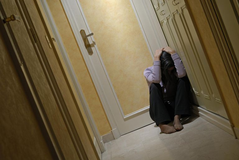 Depressed woman sitting in corridor with head in hands