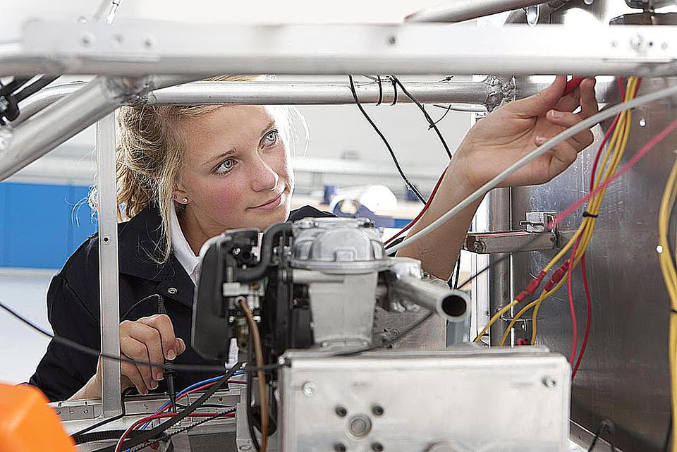 Student constructing electric vehicle prototype in vocational school