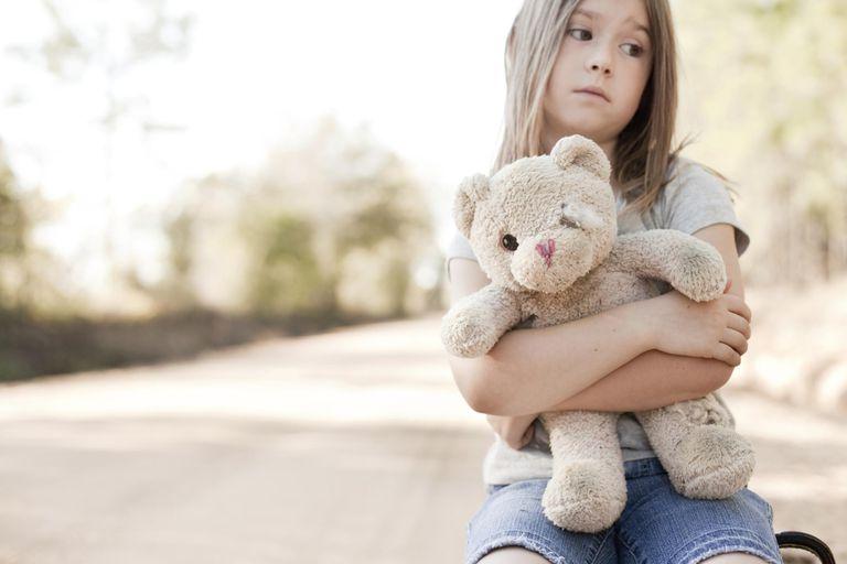 Sad Young Girl Hugging Old, Raggedy Teddy Bear