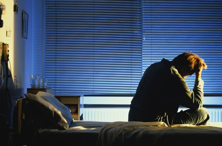 Distressed looking man sitting on hospital bed, head in hand, night