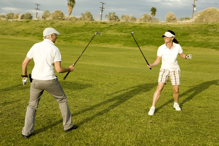 Two golfers pretend sword fight, but the golf game Defender is about defending the hole with your score, not your sword.