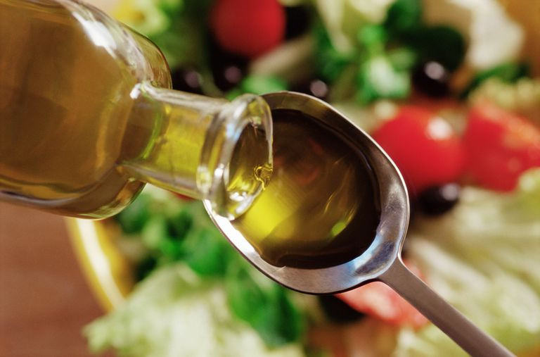 Olive oil being poured on a spoon