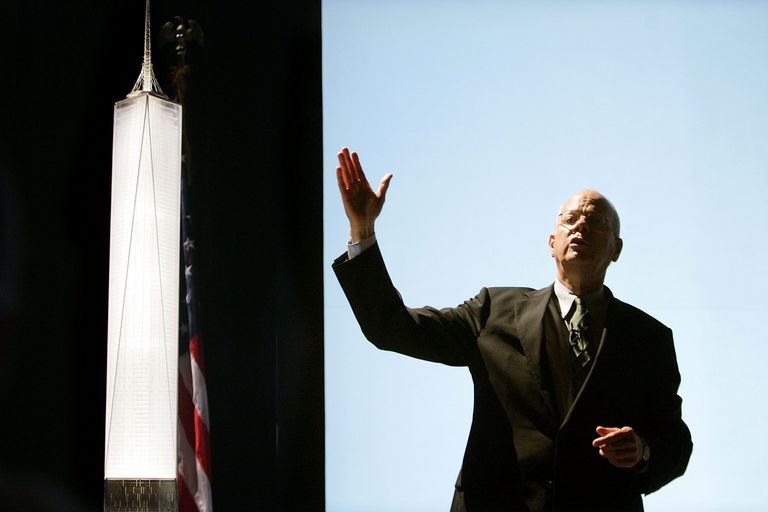 gesturing man explaining a skyscraper design in front of a model and projection screen