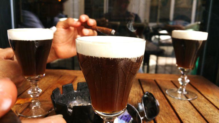 Man Smoking With Irish Coffee On Table At Cafe